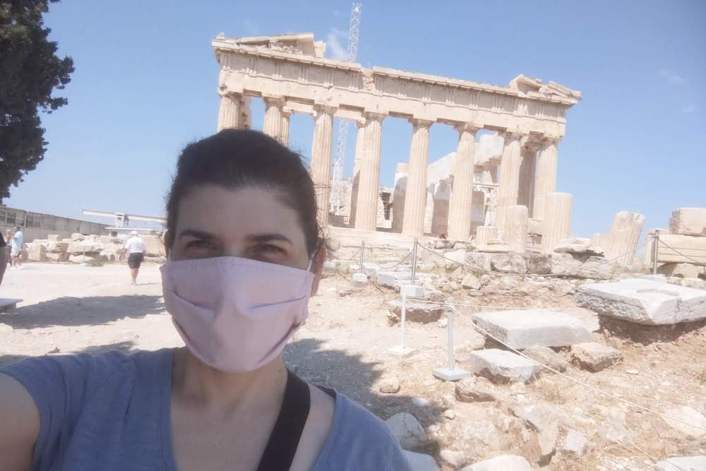 selfie of a woman wearing a mask in front of the Parthenon at the Acropolis in Athens Greece