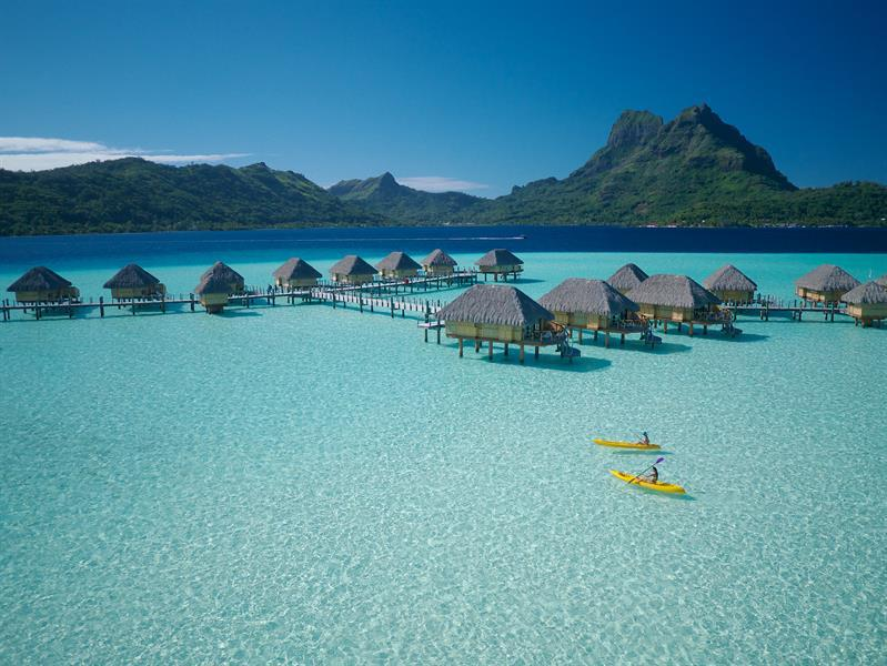 overwater bungalows in Bora Bora with green mountain in background and kayakers in foreground and very clear ocean