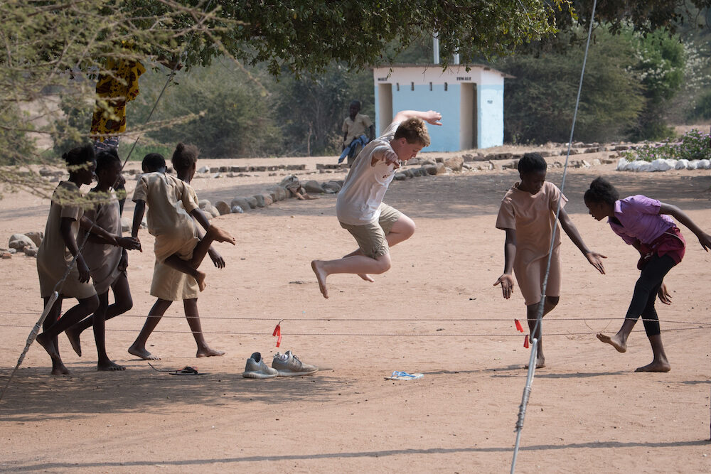 tourist boy jumping rope with local kids at a school in Chiawa Zambia