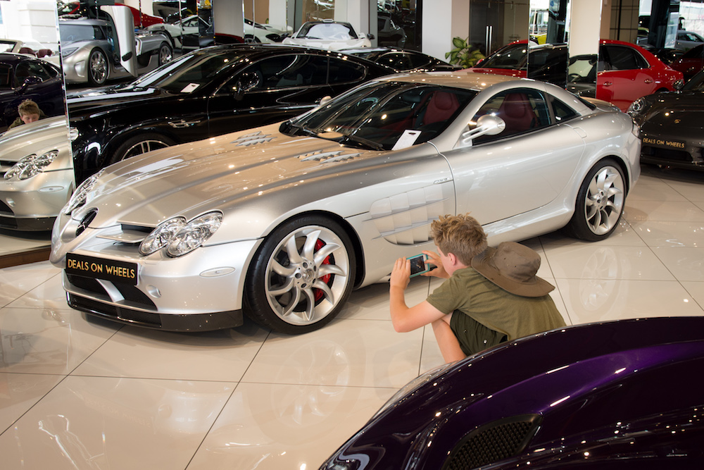 teenage boy taking photos of silver supercar in Dubai at Deals on Wheels auto store