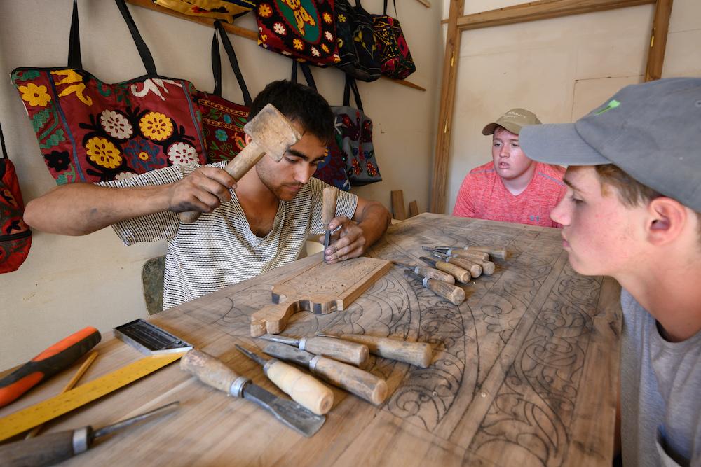 American teenage boy traveler gets woodworking lesson from local craftsman in Khiva Uzbekistan