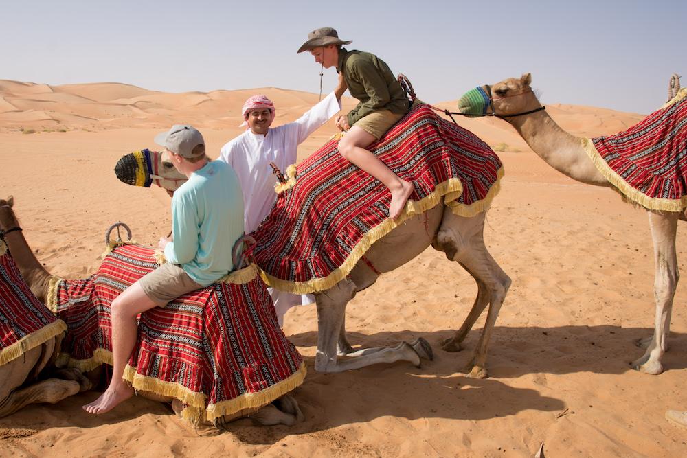 Abu Dhabi teenage boy tourist getting up on camel