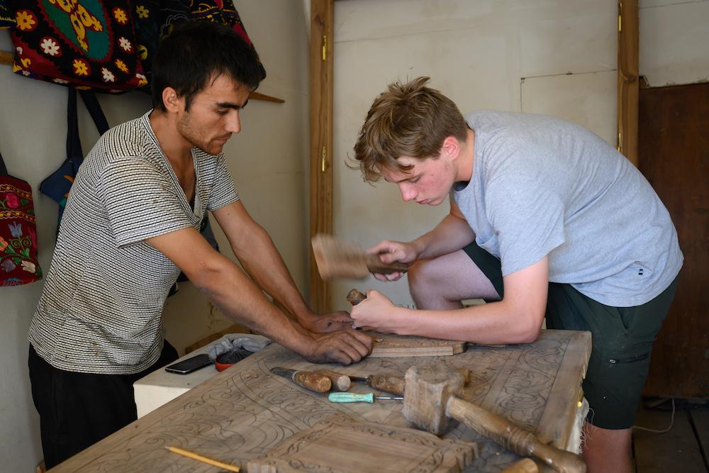 American teenage boy traveler gets ddrum making lesson from local craftsman in Khiva Uzbekistan