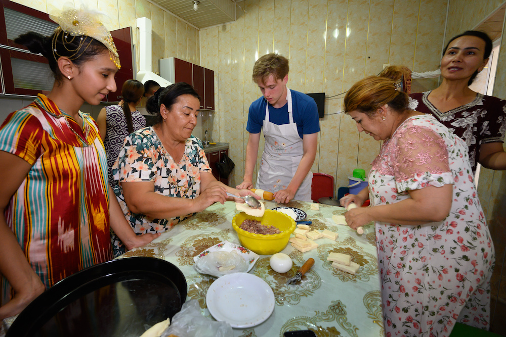 American teenage boy traveler learns how to make baklava in kitchen of local Uzbek woman with other Uzbek women in a kitchen in Bukhara Uzbekistan