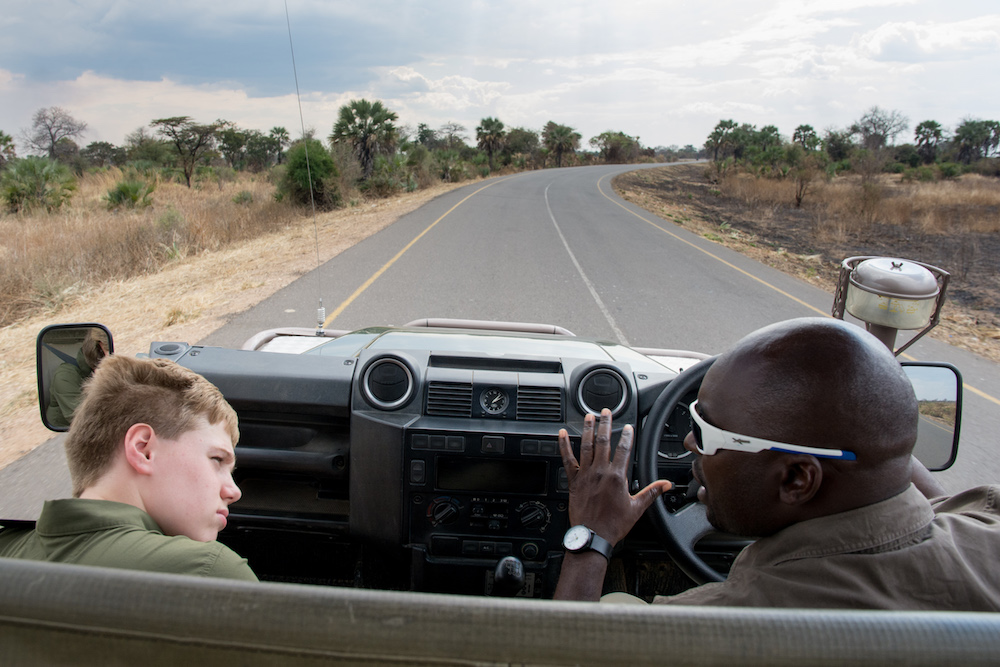 view from a car driving on a road in Zambia, a white tourist boy and an African driver