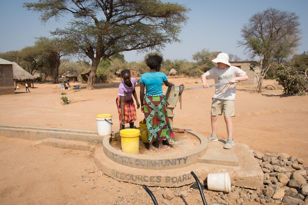 kids at a water pump in Chiawa Zambia