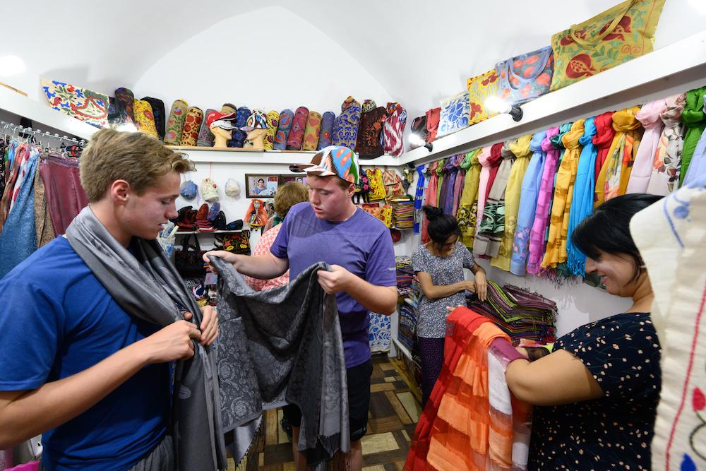 american teenage boy tourists trying on scarves in bhukara Uzbekistan shop