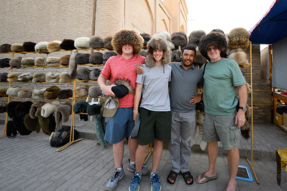 american teenage boy tourists trying on hats at a shop in Uzbekistan and posing smiling with local owner