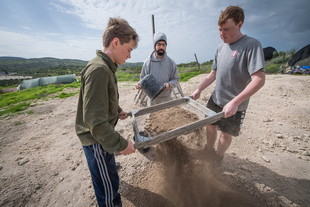 two teenage boy tourist sifting sand for artifacts at Tel Maresha Israel