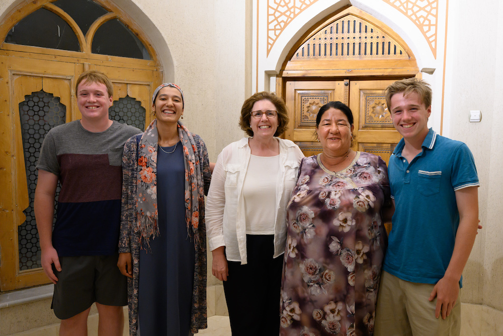 American traveler family poses with a woman in Bukhara Uzbekistan