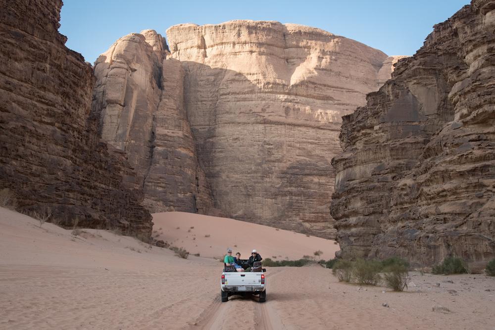 tourist family driving truck in desert of Wadi Rum jordan between two rock walls