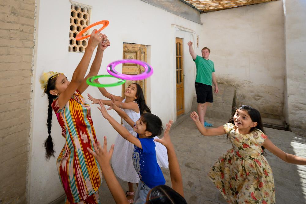 american teenagers and Uzbek children playing with flying rings in Uzbekistan