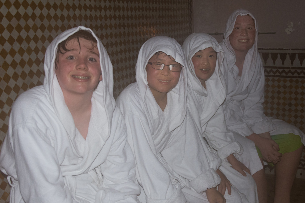 four boys wrapped in robes and towels in a hammam in Morocco