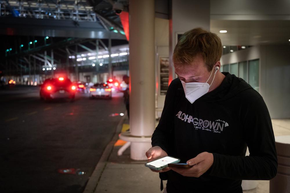 teenager at airport at night wearing mask and looking at 2 phones