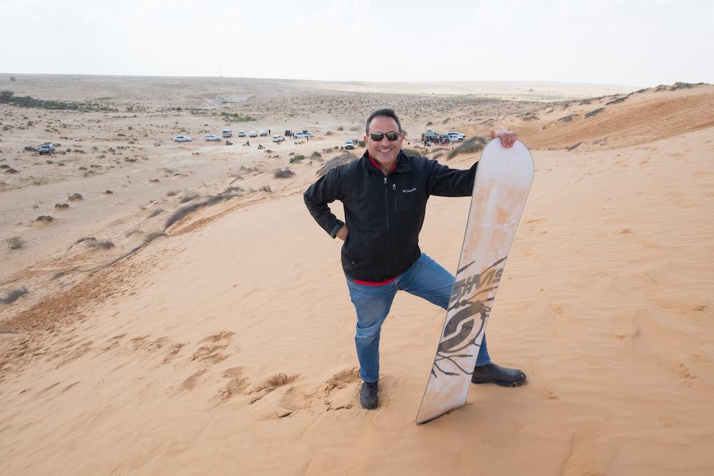man holding a sandboard in Negev desert Israel