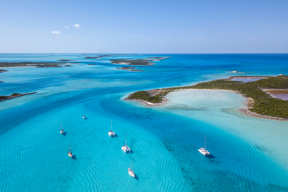 aerial view of islands an ocean The Exumas, Bahamas with catamarans dotting the water