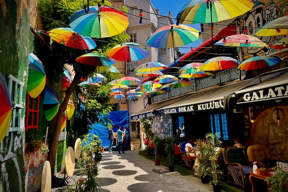 rainbow umbrellas hover over a street of shops and restaurants in Istanbul turkey