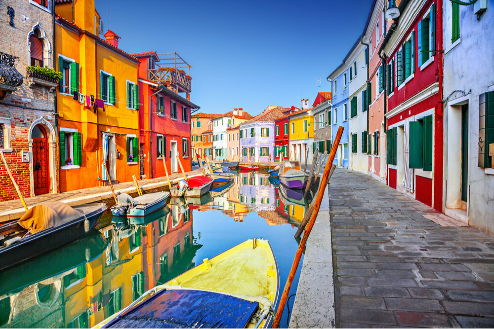 Colorful houses and boat on a canal in Burano, Venice, Italy